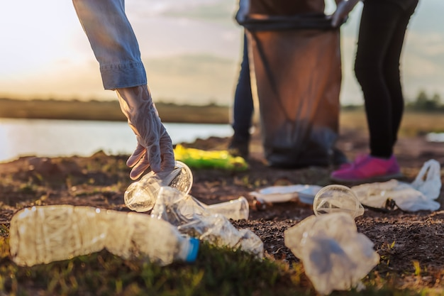 People volunteer keeping garbage plastic bottle into black bag at park near river in sunset Premium Photo