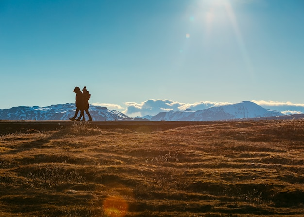 People walking in a field with beautiful snowy hills Free Photo