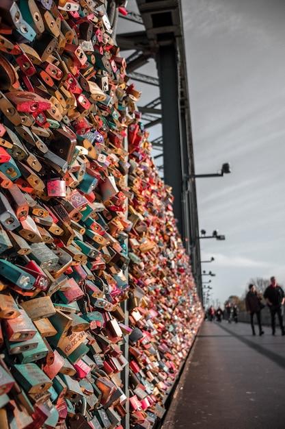 Люди идут по тротуару с разноцветными замками на заборе Бесплатные Фотографии