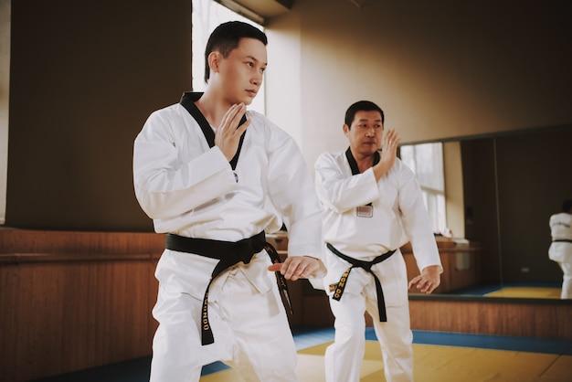 People do warm-up exercises before starting karate training. Premium Photo