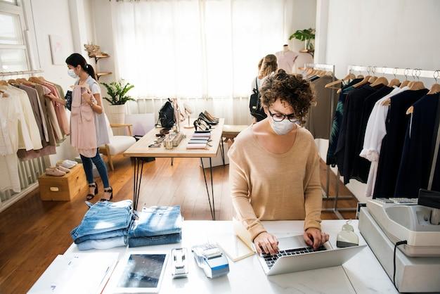 Люди в маске в магазине одежды делают покупки в новой норме Бесплатные Фотографии
