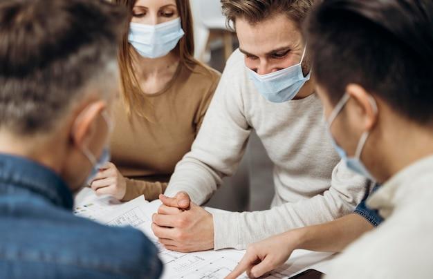 Persone che indossano maschere mediche al lavoro Foto Gratuite