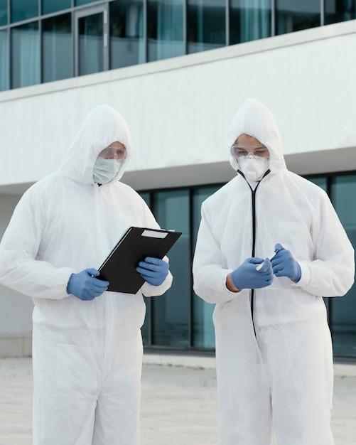 Persone che indossano tute di prevenzione contro un rischio biologico Foto Gratuite