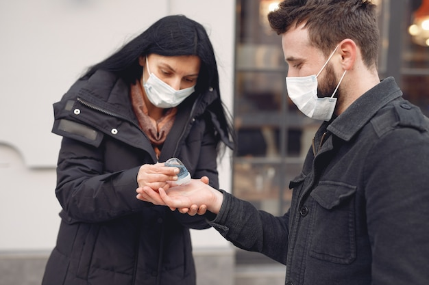 People wearing a protective mask standing on the street while using alcohol gel Free Photo