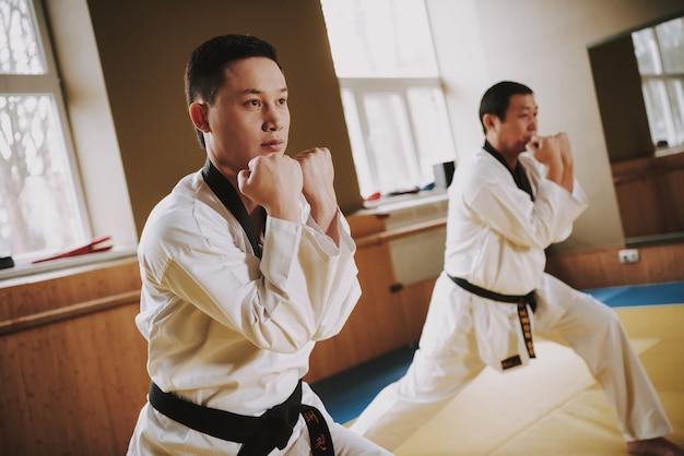 People in white kimono working out racks with jiu jitsu. Premium Photo