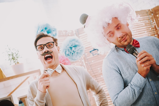 People with bow ties singing karaoke songs at party. Premium Photo