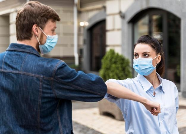 Люди в масках бьют локтями на открытом воздухе Бесплатные Фотографии