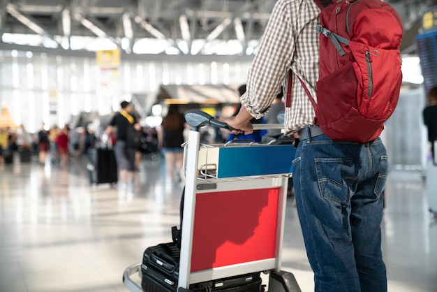 People with luggage in cart at airport. Premium Photo