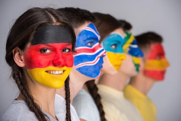 Люди с государственными флагами нарисованы на лицах. Premium Фотографии