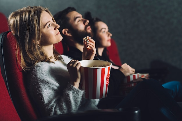 People with popcorn enjoying movie Free Photo