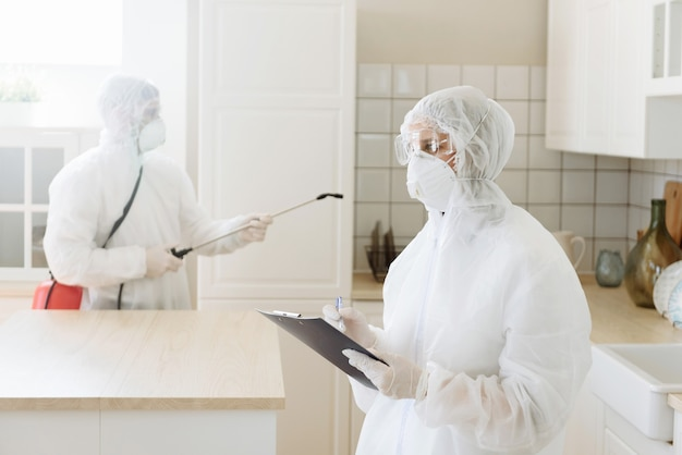 People with protective equipment are sanitized with a spray gun. surface treatment due to coronavirus disease covid-19. Premium Photo
