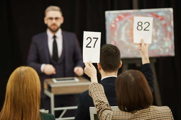 People with signs at auction Premium Photo