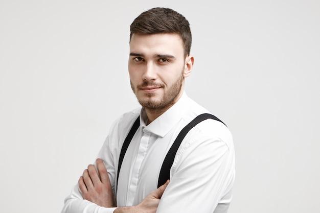 Persone, lavoro, lavoro, carriera e concetto di occupazione. foto di attraente giovane manager maschio prospero sicuro di sé in posa in studio con le braccia incrociate e fissando la telecamera con un sorriso sicuro Foto Gratuite