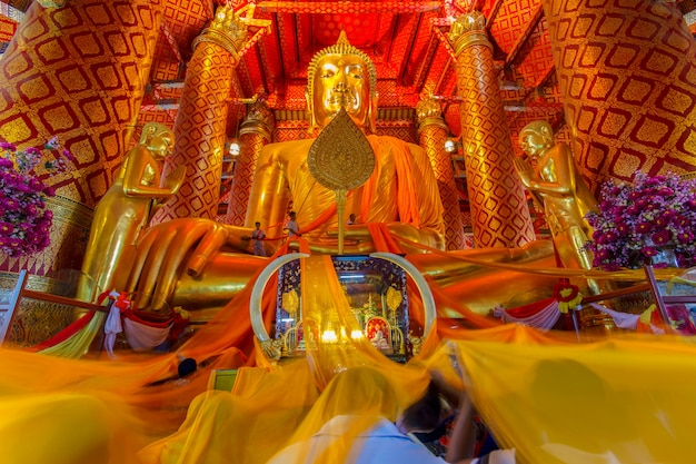 People work with cloth on buddha image in wat phanan choeng temple Premium Photo