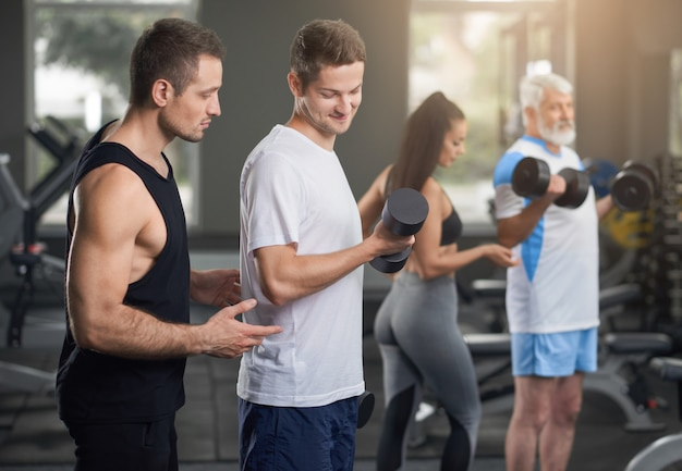 People working out in gym with personal trainers. Premium Photo