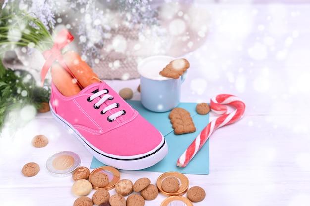 Традиционный голландский праздник для детей синтерклаас. pepernoten и традиционные сладости strooigoed, морковь в ботинке и молоко с печеньем. Premium Фотографии