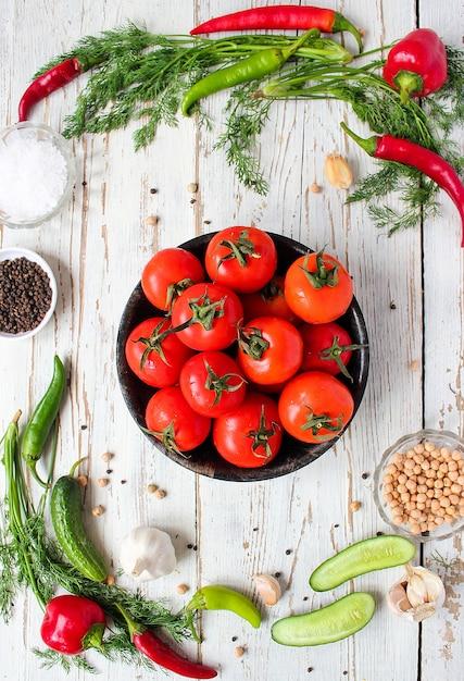 緑と赤と唐辛子、ピーマン、黒胡pepper、塩、クローズアップ、健康的な概念と白い木製テーブルの上の黒い皿に新鮮な有機赤いトマト 無料写真