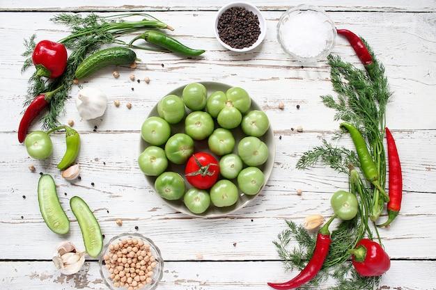 緑のトマト、緑と赤と唐辛子、フェンネル、塩、黒胡pepper、ニンニク、エンドウ豆と白い木製のテーブルのピクルス、クローズアップ、健康概念、平面図、フラットレイアウト 無料写真