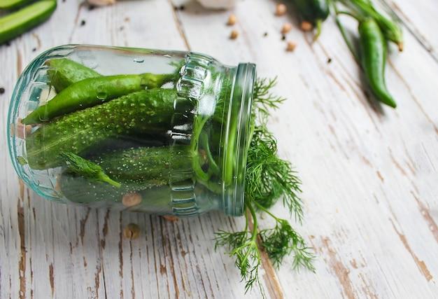 新鮮な有機きゅうりピクルスの瓶に緑と赤と唐辛子、フェンネル、塩、黒胡pepper、ニンニク、エンドウ豆、グリーントマト、クローズアップ、健康概念、平面図、フラットレイアウトと白い木製のテーブルの上 無料写真