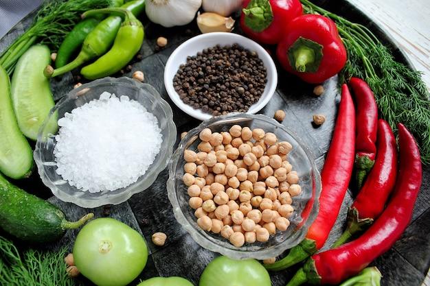 緑と赤と唐辛子、フェンネル、塩、黒胡pepper、ニンニク、エンドウ豆、クローズアップ、健康概念、平面図、フラットレイアウトと白い木製のテーブルのピクルス 無料写真
