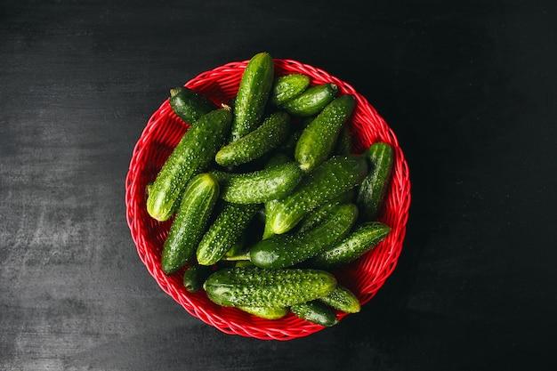 緑と赤と唐辛子、フェンネル、塩、黒胡pepper、ニンニク、エンドウ豆と白い木製テーブルの上の赤いバスケットに新鮮な有機キュウリ、クローズアップ、健康概念、平面図、フラットレイアウト 無料写真