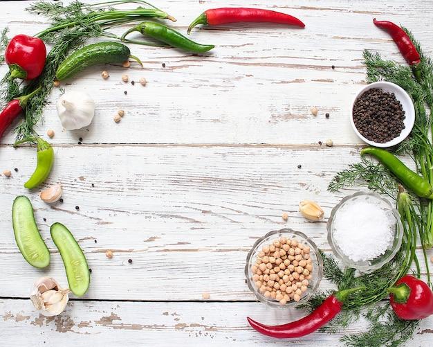 緑と赤と唐辛子、フェンネル、塩、黒胡pepper、ニンニク、エンドウ豆、クローズアップ、健康概念、平面図、フラットレイアウトと白い木製のテーブルの上のピクルスの背景 無料写真
