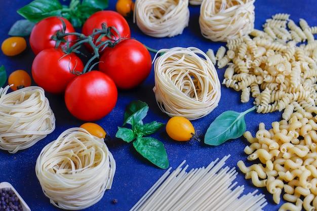 イタリア料理 。イタリア料理。原材料トマト、イエローチェリートマト、フレッシュバジル、黒胡pepperコーン、各種パスタ。 無料写真