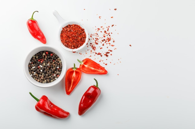 Peppercorns with chili powder in scoop and red peppers in a plate on white wall, top view. Free Photo