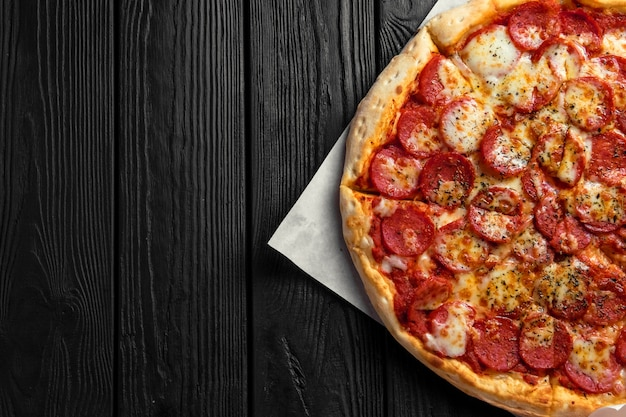 Pepperoni pizza on dark black wooden board, top view, place for text, traditional italian pizza Premium Photo