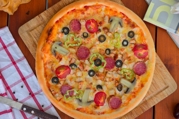 Pepperoni pizza with bell pepper, tomato slices, mushroom and olives Free Photo
