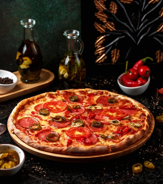 Pepperoni pizza with olives on wooden board Free Photo