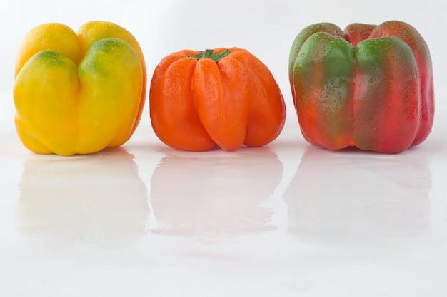 Перцы разных цветов с каплями воды на белом Premium Фотографии