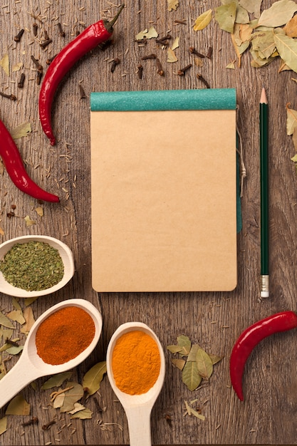 Peppers, spices in spoons, notebook and pencil Premium Photo