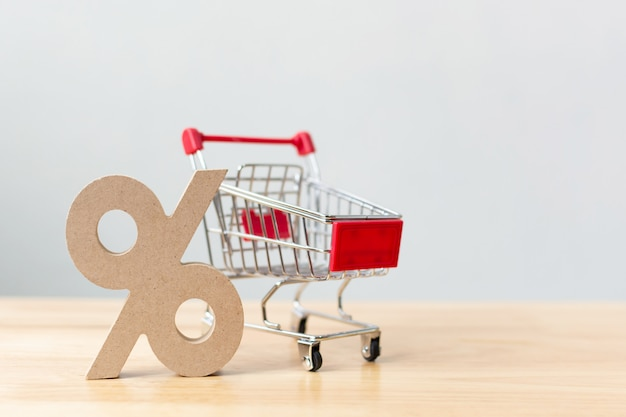Percentage sign symbol icon wooden and shopping cart on wood table Premium Photo