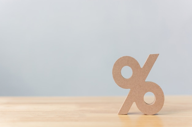 Percentage sign symbol icon wooden on wood table with white background Premium Photo
