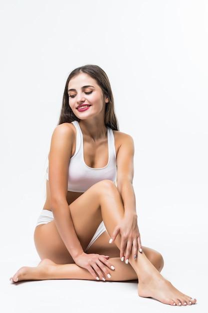 Corpo perfetto, bella donna. ragazza modello con bel corpo - gambe, braccia, spalle, seduta su un piano. donna di bellezza e salute in biancheria intima bianca che tocca la sua pelle. Foto Gratuite