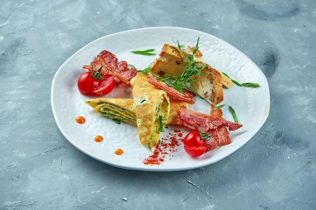 完璧な朝食-白い皿にほうれん草、ベーコン、焼きたてのパンとスクランブルエッグ。おいしいオムレツ Premium写真