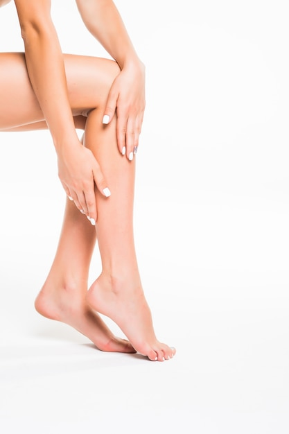 Идеальные женские ножки, изолированные на белой стене Бесплатные Фотографии