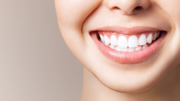 Perfect healthy teeth smile of a young woman. teeth whitening. dental clinic patient. image symbolizes oral care dentistry, stomatology. dentistry image. Premium Photo