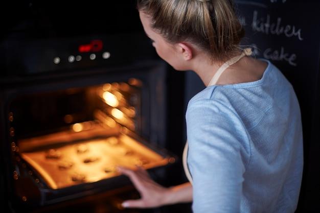 彼女のお気に入りのクッキーを焼く完璧な主婦 無料写真