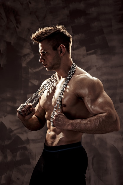 The perfect male body - awesome bodybuilder posing. hold a chain with tattoo Premium Photo