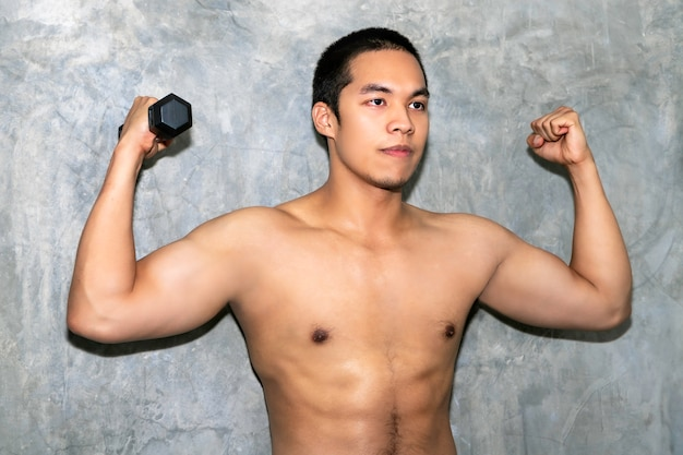 Perfect strong bodybuilder athletic asian man workout arm with dumbbell on background. Premium Photo