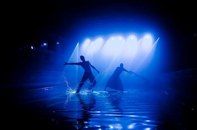 클럽 조명을 배경으로 댄스 그룹의 물 위에서 공연. 프리미엄 사진