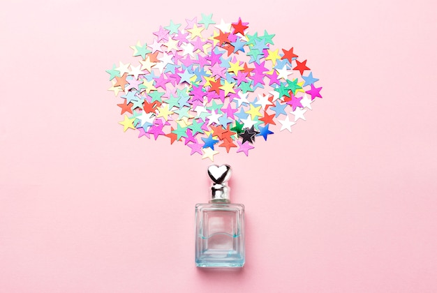 Perfume bottle and confetti on pink background, flat lay Premium Photo