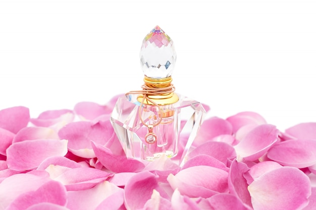 Perfume bottle with necklace among flower petals. perfumery, cosmetics, fragrance collection Premium Photo
