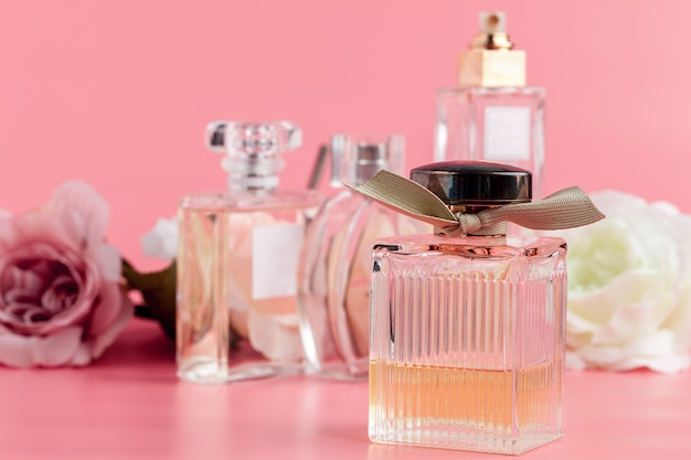 Perfume bottle with roses on pink fabric Premium Photo