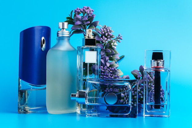Perfume bottles with flowers on a light blue Premium Photo