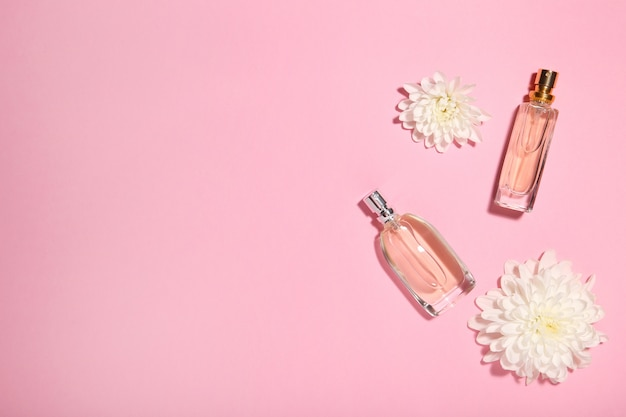 Perfume bottles with flowers on pink Premium Photo