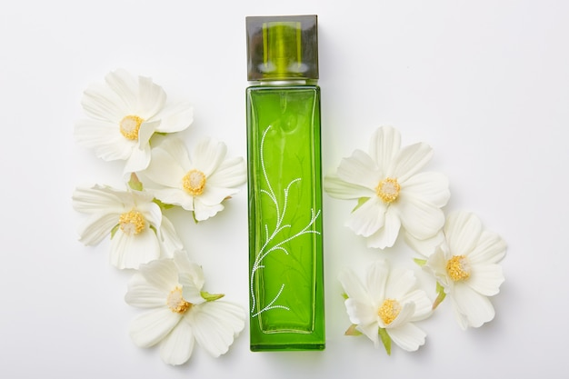 Perfume for women in green bottle and flowers around isolated on white. pleasant aromat or odor. floral fragrance Free Photo