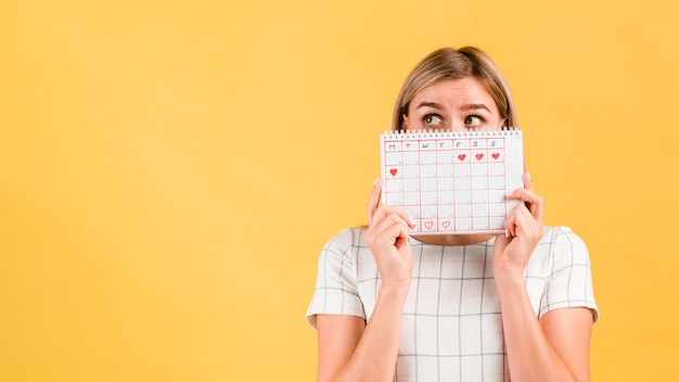 Period calendar with drawn heart shapes and woman covering her face Premium Photo